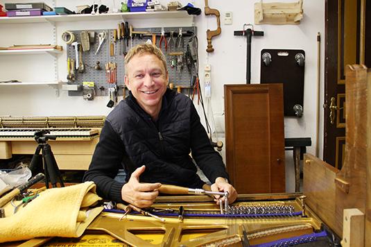 Thomas Stieler in der eigenen Klavierwerkstatt beim Klavier stimmen.